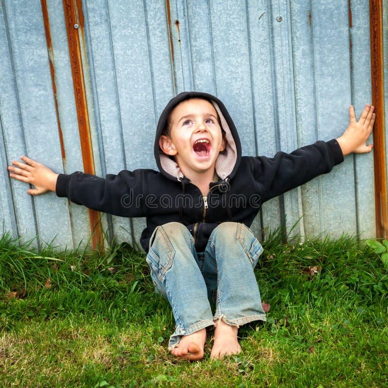愉快的呼喊的无家可归的男孩 免版税库存图片