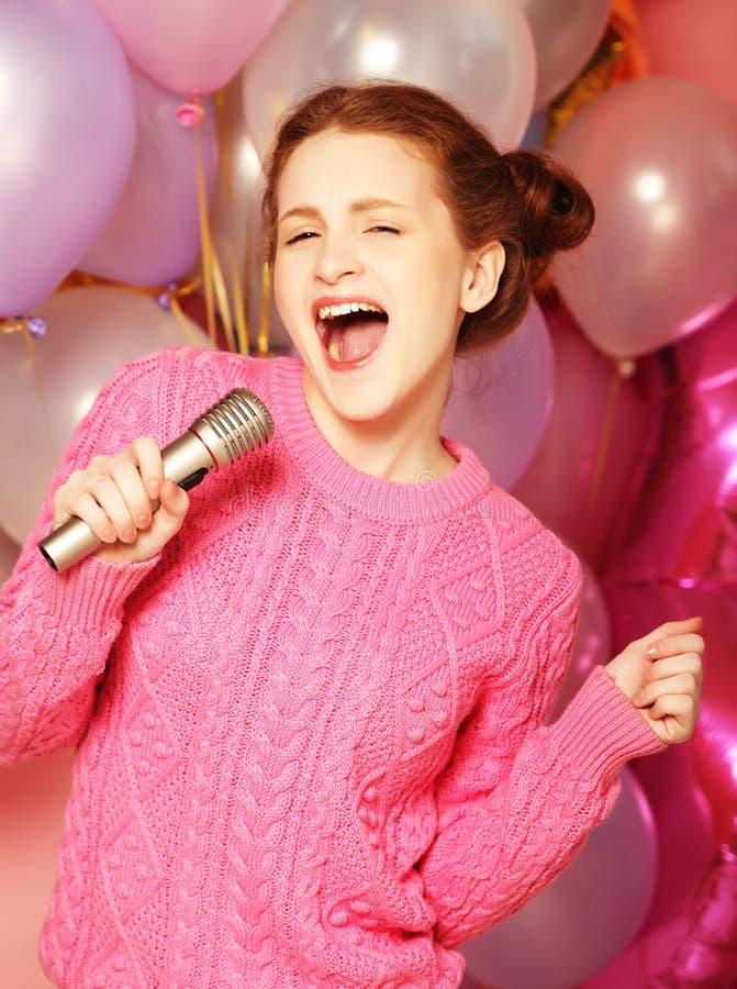 愉快的唱歌的女孩 有话筒的秀丽妇女在backgroun 免版税图库摄影