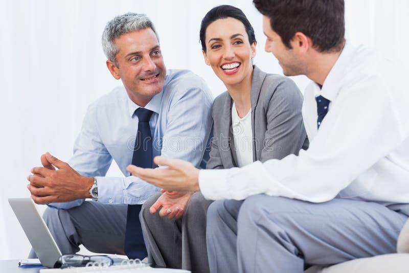 愉快的商人与他们的在沙发的膝上型计算机一起使用 免版税库存图片