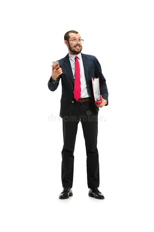 愉快的商人在手中谈话在有文件夹的电话被隔绝在演播室射击的白色背景 免版税库存图片