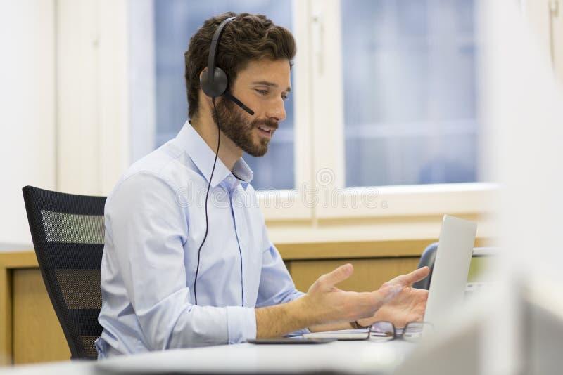 愉快的商人在电话的办公室,耳机, Skype 免版税库存图片