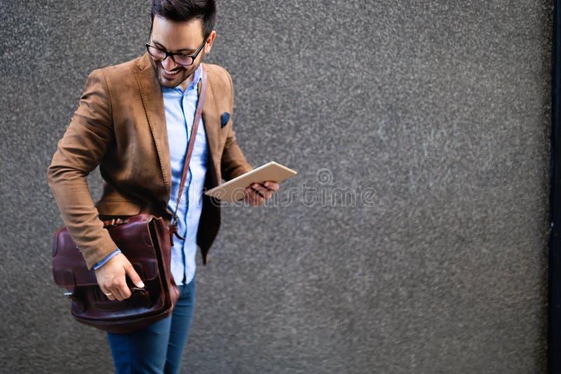 愉快的商人在都市的办公室外面 企业工作的年轻白种人人藏品片剂 免版税库存图片