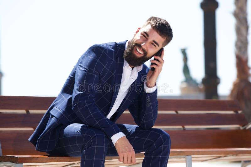 愉快的商人坐长凳谈话在手机 图库摄影