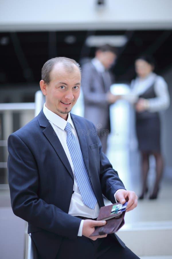 愉快的商人打开钱包 在办公室背景的照片  免版税库存图片