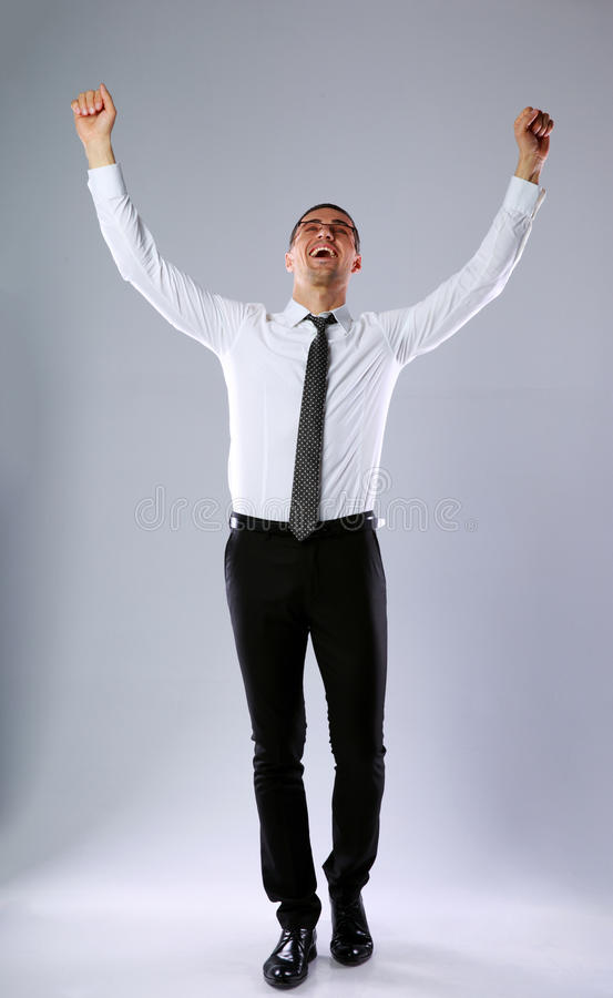 愉快的商人用被举的手  免版税库存图片