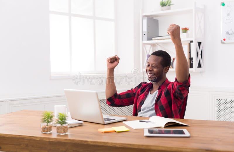 愉快的商人胜利 优胜者,黑人在办公室 免版税库存照片