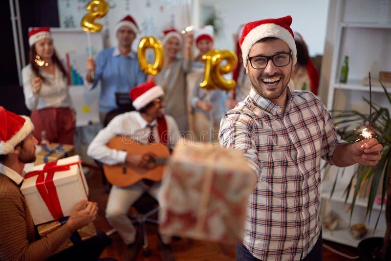 愉快的商人获得乐趣在圣诞老人帽子和交换礼物在与他的同事的Xmas党 免版税图库摄影