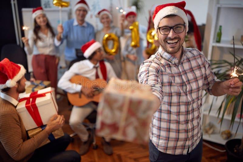 愉快的商人获得乐趣在圣诞老人帽子在与他的同事的Xmas党 免版税库存图片