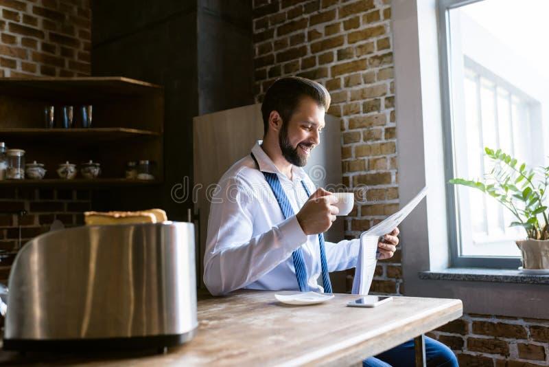 愉快的商人读书报纸和饮用的咖啡在厨房 免版税库存图片
