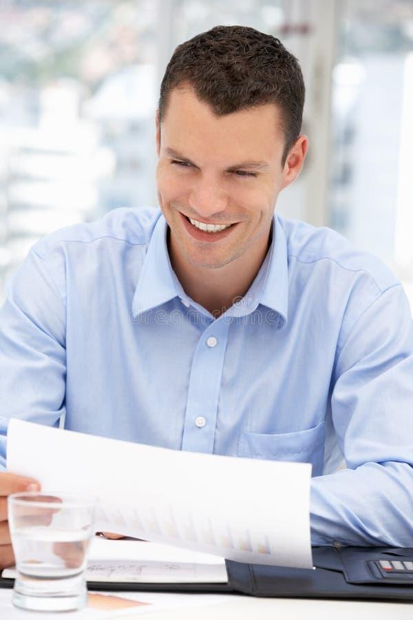 愉快的商人读取附注在办公室 免版税图库摄影