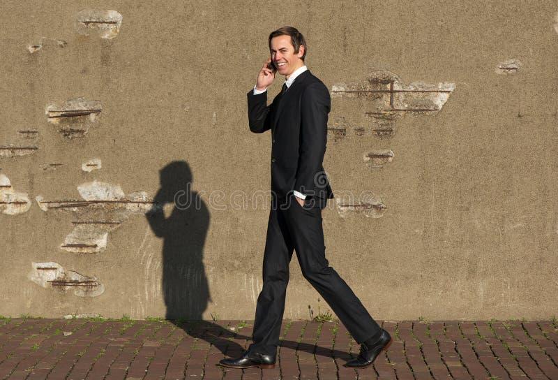 愉快的商人走和谈话在手机 免版税库存照片