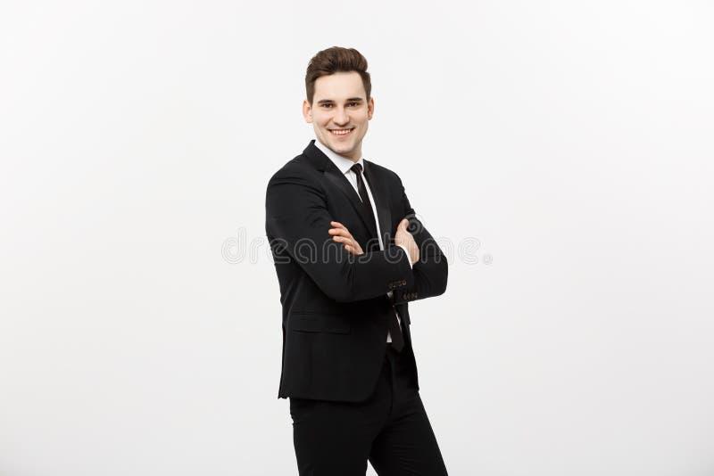 愉快的商人隔绝了-站立与横渡的胳膊的成功的英俊的人被隔绝在白色背景 免版税库存图片