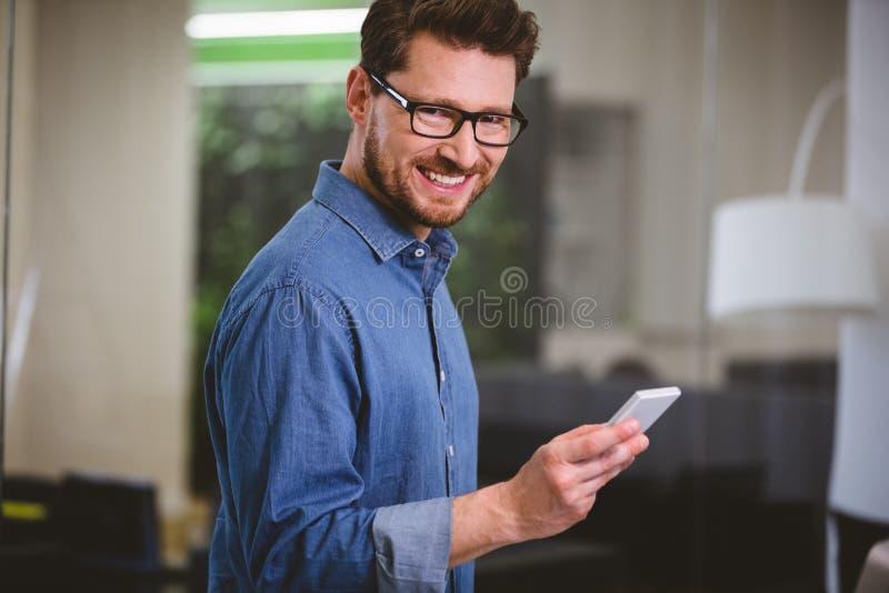 愉快的商人画象与手机的在创造性的办公室 免版税图库摄影