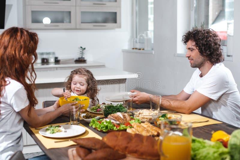愉快的喂养她的孩子的父母由健康食物 免版税库存图片