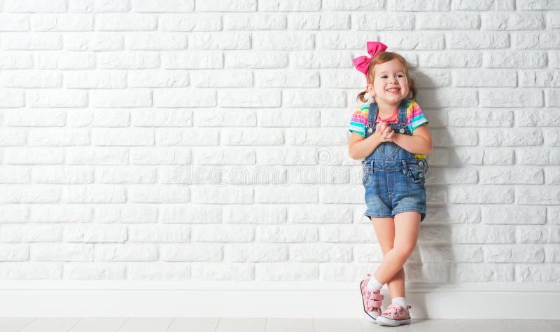 愉快的嘲笑空白的砖墙的儿童小女孩 免版税库存图片