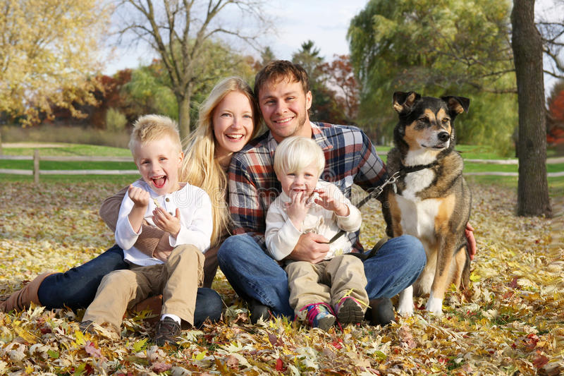 愉快的四口之家人和狗外面在秋天 库存图片