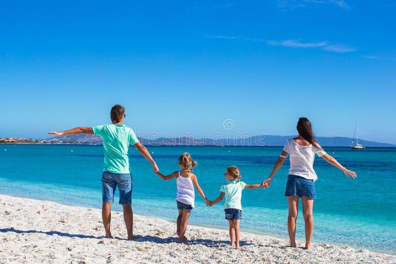 愉快的四口之家在夏天海滩假期时 库存图片