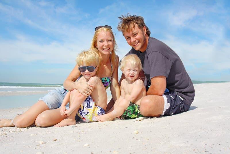 愉快的四口之家在海滩 免版税库存图片