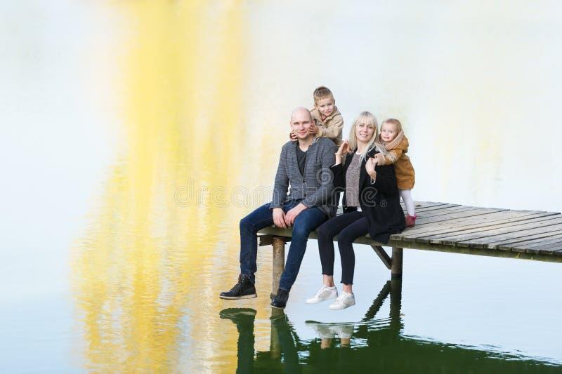 愉快的四口之家坐木码头在温暖的秋天天 免版税库存图片