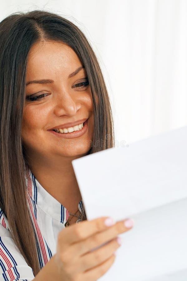 愉快的在一封信件的企业家妇女读的好消息在沙发 免版税库存图片