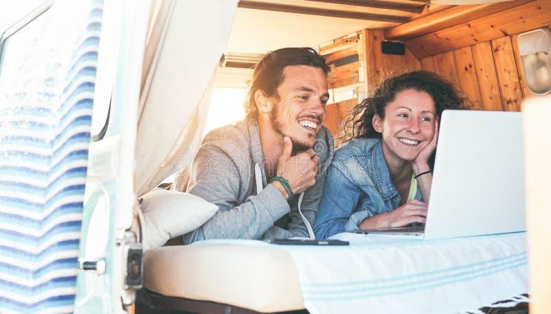 愉快的在他们的计算机里面微型货车的夫妇观看的录影在日落-使用膝上型计算机的旅行夫妇在他们的旅途期间 免版税库存照片