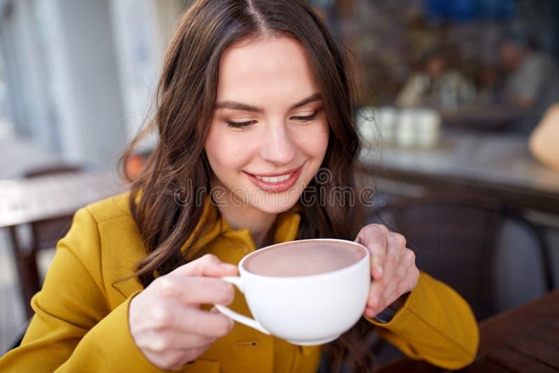 愉快的在城市街道咖啡馆的妇女饮用的可可粉 免版税库存图片