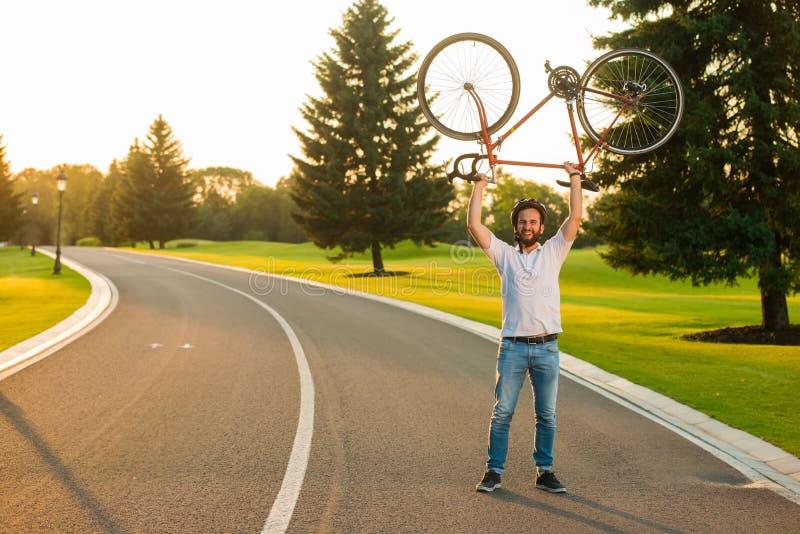 愉快的在头上的骑自行车者举的自行车 免版税库存照片
