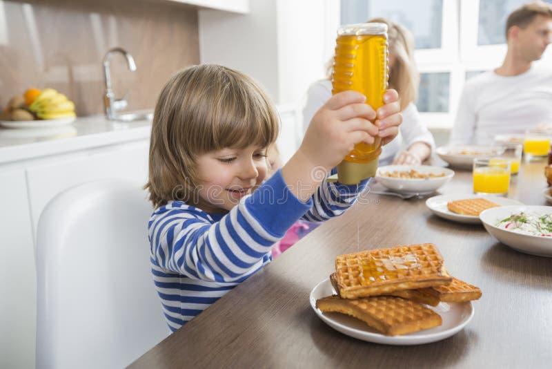 愉快的在奶蛋烘饼的男孩倾吐的蜂蜜,当食用与家庭时的早餐 库存照片