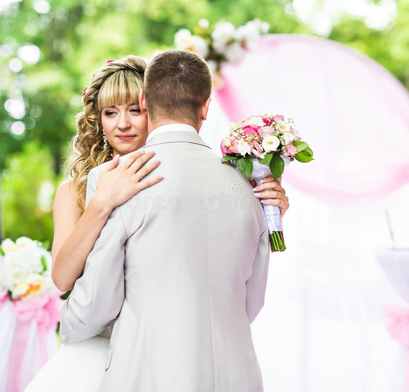 愉快的在婚礼走道的新婚佳偶浪漫夫妇跳舞有桃红色装饰和花的 免版税库存图片