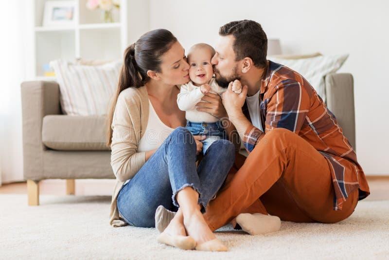 愉快的在家亲吻婴孩的母亲和父亲 免版税图库摄影