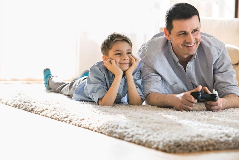 愉快的在家打在地板上的父亲和儿子电子游戏 免版税库存照片
