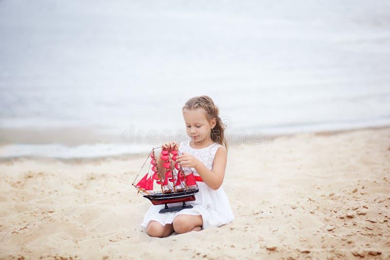 ?? 愉快的在开放沙子的童年无忧无虑的比赛 休息女孩的概念在海的有船的 女孩的画象 库存图片