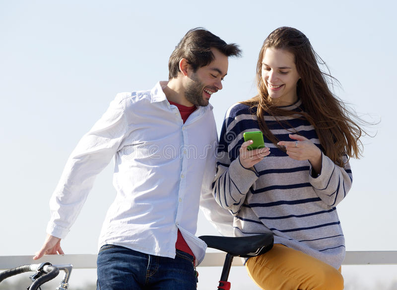 愉快的在手机的夫妇外部看的正文消息 免版税库存图片