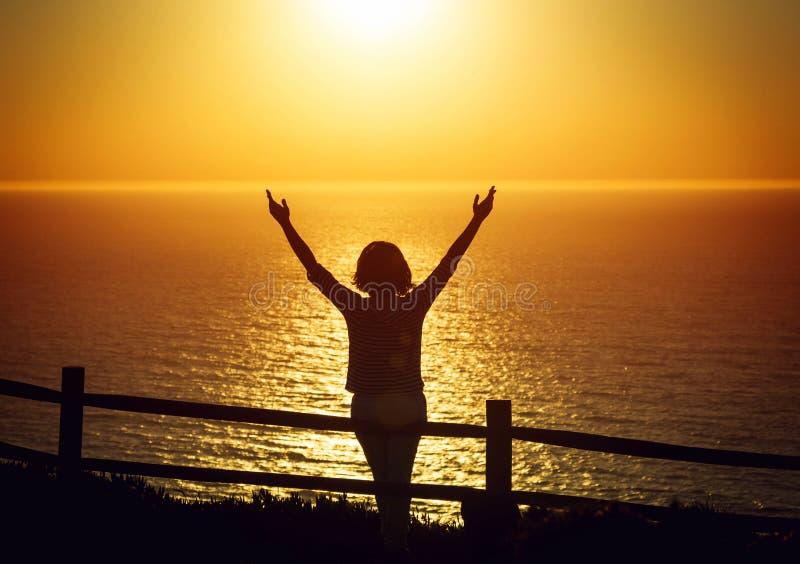 愉快的在日落下的妇女开放胳膊在海边 免版税库存图片