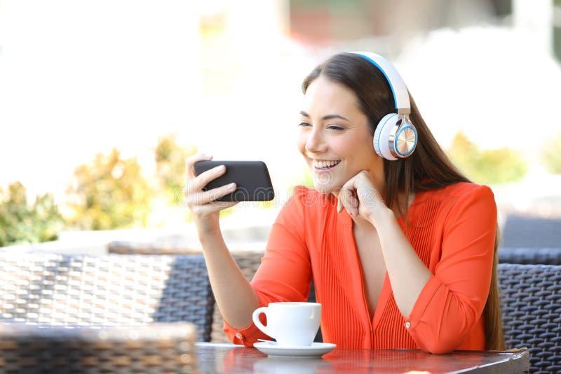 愉快的在智能手机的妇女观看的媒介在餐馆 免版税库存图片