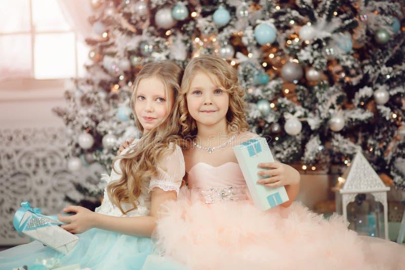 愉快的在树附近的儿童姐妹开放不可思议的礼物家在礼服 快活的圣诞节 免版税库存图片