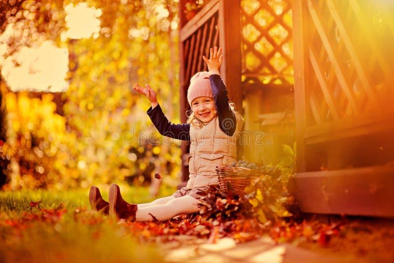 愉快的在步行的儿童女孩投掷的叶子在晴朗的秋天庭院里 免版税库存图片
