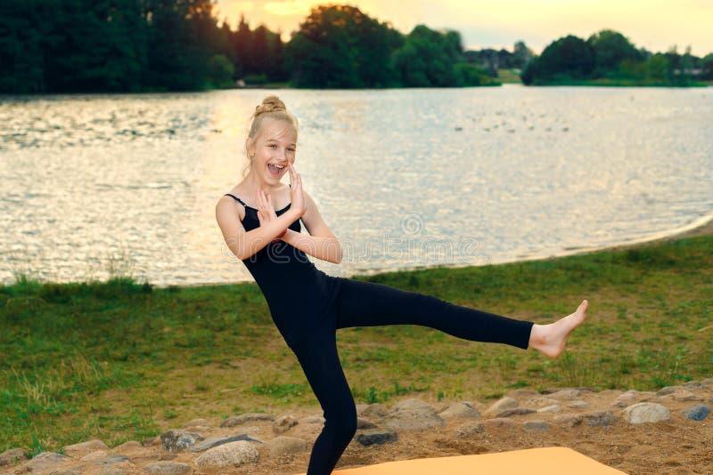 愉快的在河岸的儿童实践的瑜伽pilates 库存照片
