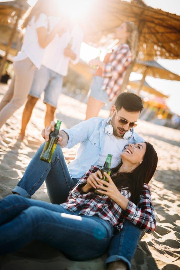愉快的在海滩的夫妇微笑的和饮用的啤酒 免版税库存图片