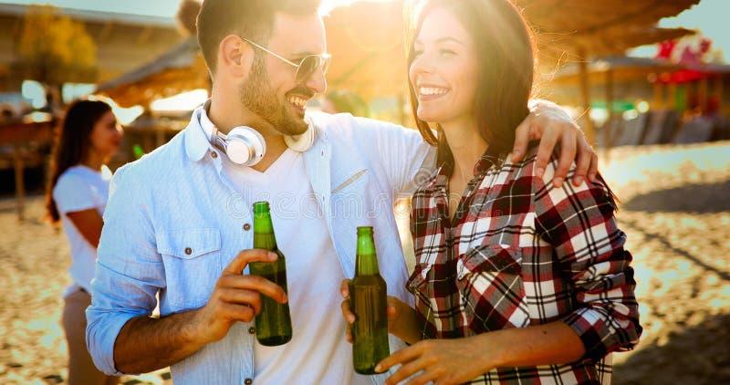 愉快的在海滩的夫妇微笑的和饮用的啤酒 库存图片