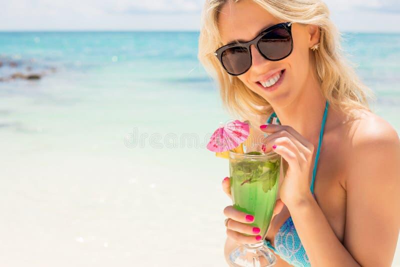 年轻愉快的在海滩的妇女饮用的mojito鸡尾酒 免版税图库摄影