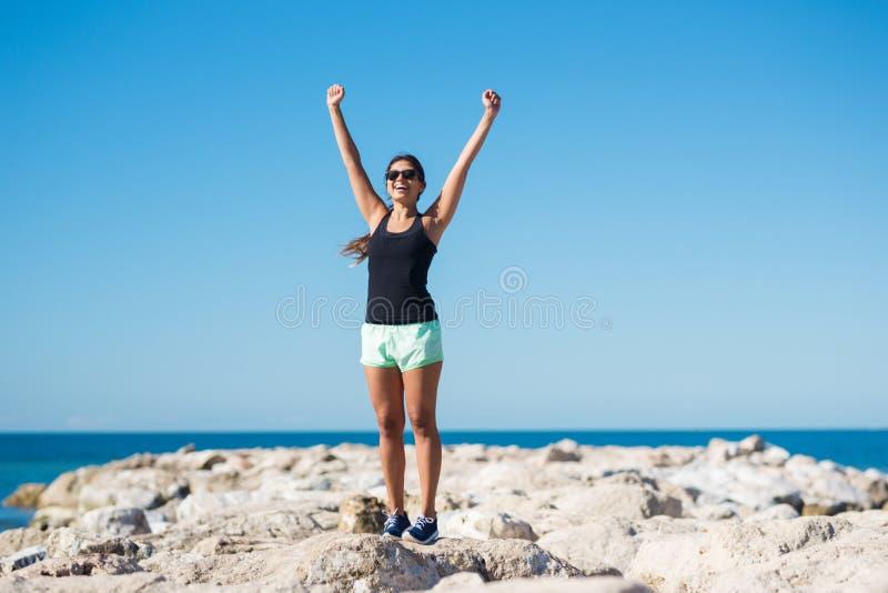 年轻愉快的在胜利姿态的妇女上升的手 免版税图库摄影