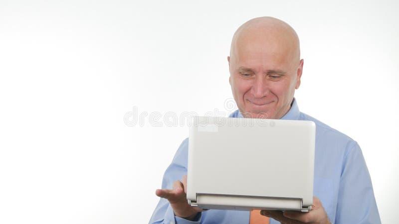 愉快的在膝上型计算机的商人图象读的财政喜讯 免版税库存照片