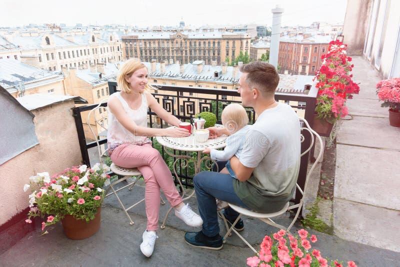 愉快的在舒适阳台的家庭饮用的咖啡 免版税库存照片