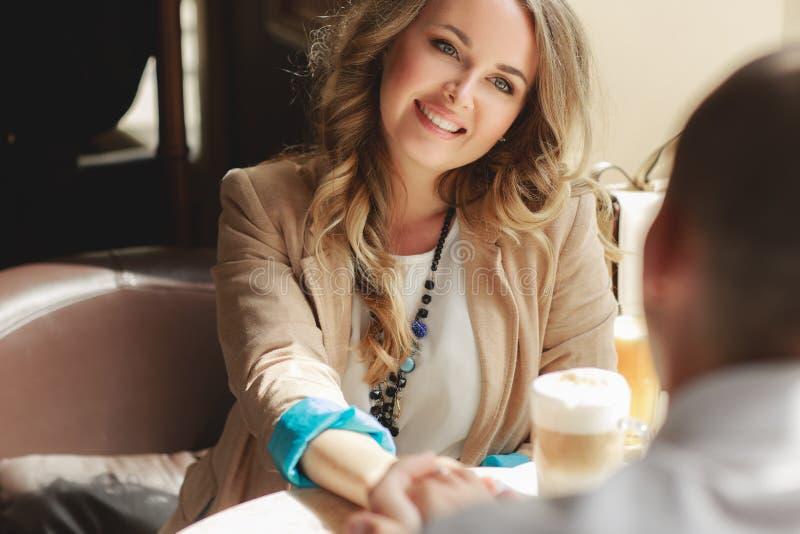 愉快的在都市café的夫妇饮用的咖啡 免版税图库摄影