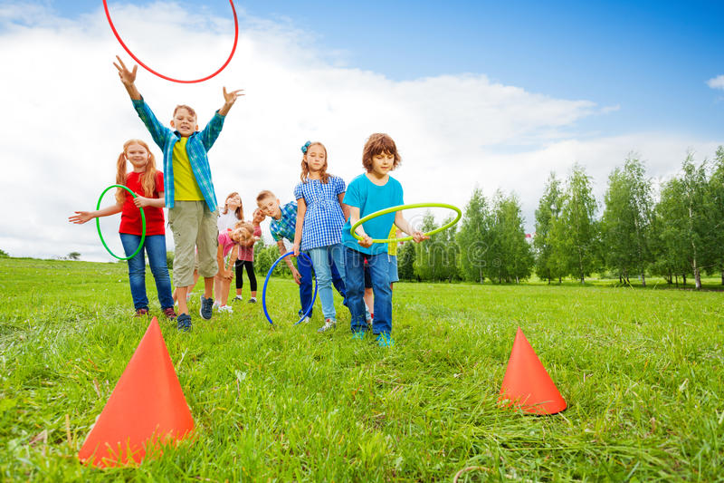 愉快的在锥体的儿童投掷五颜六色的箍 图库摄影