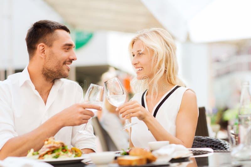 愉快的在餐馆休息室的夫妇使叮当响的玻璃 库存照片