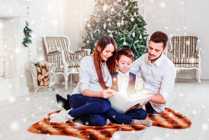 愉快的在Xmas树附近的家庭读书圣诞节童话 圣诞树和当前礼物盒装饰的客厅 库存图片