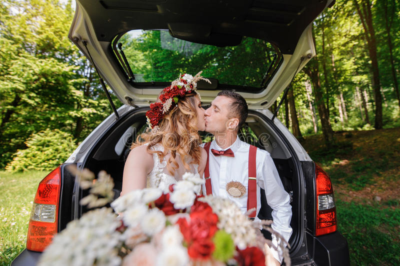 愉快的坐在汽车的后车箱的新娘和新郎 库存照片