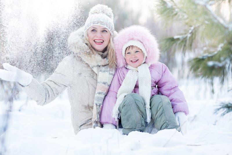愉快的坐在雪的家庭母亲和女儿 免版税库存照片